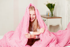 Young girl lying on the bed under the covers Stock Photos