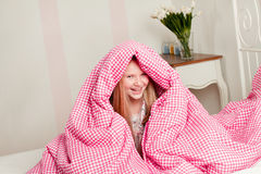 Young girl lying on the bed under the covers Royalty Free Stock Photos