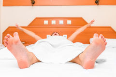 Young girl lying in bed yawning Royalty Free Stock Photo