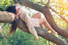Young girl lying on the bench in the forest. Young girl lying on the tree bench in the daylight Royalty Free Stock Photos