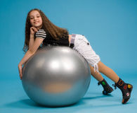 Young girl lying on a big rubber ball Royalty Free Stock Photography