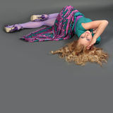 Young girl lying in the casual pose. Gray background Stock Photos