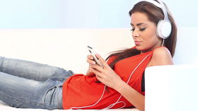 Young girl lying on couch listen to the music stock footage