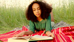 Young girl lying on cover and reading