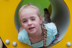 Young girl lying in crawl tube Stock Photography