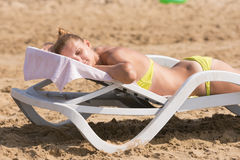 Young girl lying on deck chair back up, turning his head and eyes closed Royalty Free Stock Image