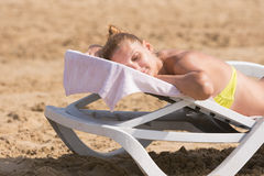 Young girl is lying on a deck chair on his stomach, his head turned and eyes closed Stock Images