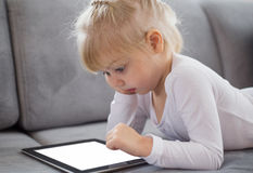 Young girl lying down on couch and playing with tablet computer Stock Photos