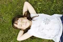 Young Girl Lying Down On The Grass Royalty Free Stock Image