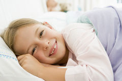 Young Girl Lying Down In Her Bed royalty free stock photography