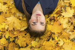 Young girl lying on fallen autumn leaves. Stock Images