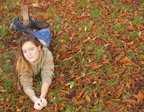 Young  girl lying on the fallen yellow leaves in autumn park. Royalty Free Stock Images
