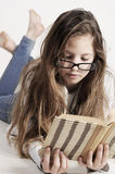 Young girl is lying on the floor with a book Royalty Free Stock Photo