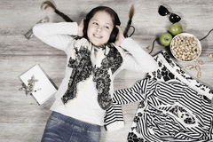 Young girl is lying on the floor and listening music Royalty Free Stock Photography