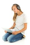 Young girl lying on the floor listening to music over white back Stock Photography