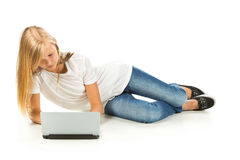 Young girl lying on the floor using laptop Stock Photos