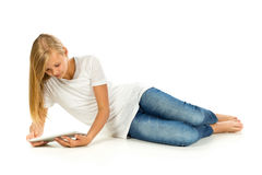 Young girl lying on the floor using tablet pc over white backgro Stock Photography