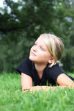 Young girl lying in the grass. Child relaxing in a park Stock Images