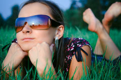 Young girl lying in grass. Young beautiful girl in sun glasses lying in green grass Stock Images