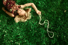 Young girl lying in grass. Young beautiful girl lying in green grass with white necklace Royalty Free Stock Photo