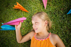 Young girl lying on grass around paper planes Stock Photo