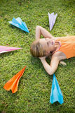Young girl lying on grass around paper planes. Happy young girl lying on grass around paper planes in park Royalty Free Stock Photo