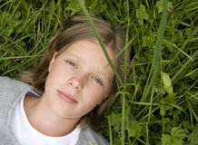 Young girl lying in the grass dreaming of ... Stock Photos