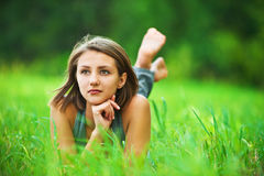 Young girl lying on grass dreaming Royalty Free Stock Images