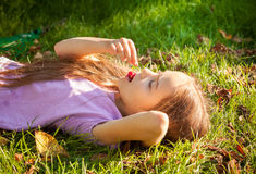 Young girl lying on grass and eating cherry outdoor Stock Photo