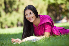 Young girl lying on the grass in the park Royalty Free Stock Photos