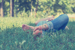 A young girl lying on the grass in the Park and resting. Concept, outdoor recreation, serenity Stock Images
