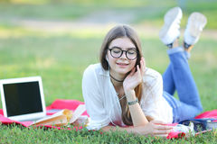 Young girl lying on the grass in the park and works at a laptop. Royalty Free Stock Photo