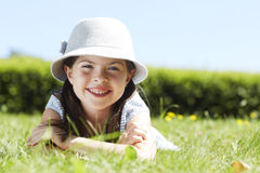 Young girl lying on grass, smiling Stock Photography