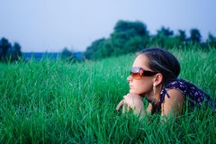 Young girl lying in green grass Stock Photography
