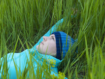 Young girl lying in green grass. Royalty Free Stock Photo