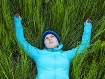 Young girl lying in green grass. Royalty Free Stock Images