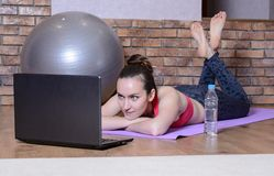 Young girl lying with hands under my head on the yoga Mat and looks at the laptop screen. Fitness at home Stock Photo