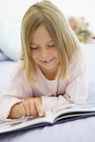 Young Girl Lying On Her Bed reading Royalty Free Stock Photos