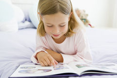 Young Girl Lying On Her Bed Reading A Book Stock Photo
