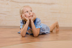 Young girl lying on her stomach daydreaming Royalty Free Stock Photos
