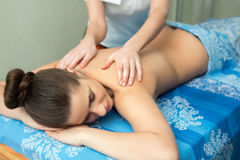 Young girl lying on her stomach having massage Stock Image