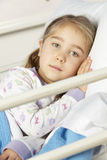 Young girl lying in hospital bed Royalty Free Stock Images
