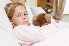 Young Girl Lying In Hospital Bed With Teddy Bear Stock Photography