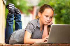 Young girl lying with a laptop Stock Photos