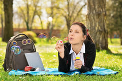Young girl lying on a meadow blowing soap bubbles Royalty Free Stock Photos