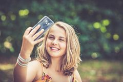 Girl with smartphone outdoors stock photography