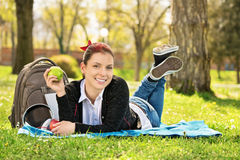 Young girl lying on a meadow holding an apple Stock Photography