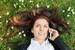 Young girl lying on a meadow talking on the phone Royalty Free Stock Image