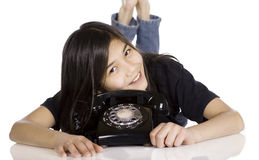 Young girl lying by old phone Stock Image