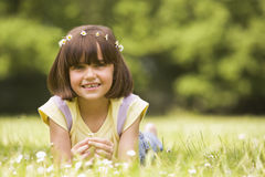Young girl lying outdoors with flowers smiling Stock Photos